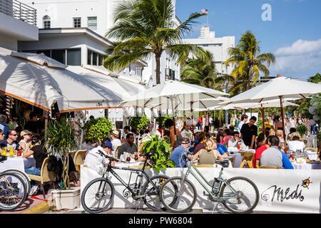 Miami Beach Florida Ocean Drive New Year's Day Art Deco District Cafe Medi restaurant alfresco al fresco dining umbrellas dine - Stock Image