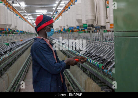 Industry and manufacturing in Africa: Textile workers producing fabric and clothing at a factory in Kampala, Uganda, using cotton grown in Africa - Stock Image