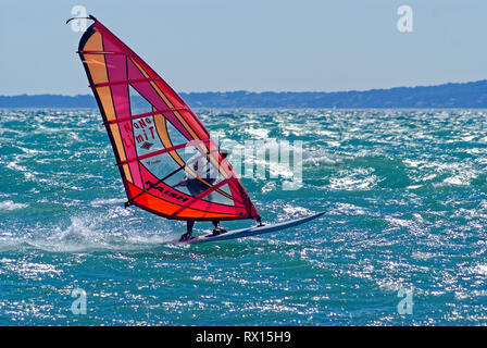 Windsurf with red sail at full speed during a mistral windy day in mediterranean sea (St Laurent du Var , France) - Stock Image