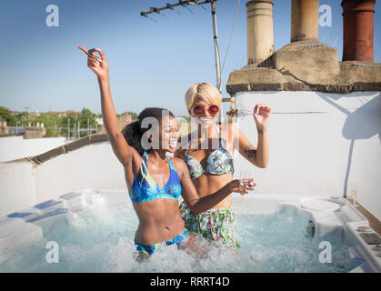 Portrait playful young women friends in bikinis dancing in sunny rooftop hot tub - Stock Image