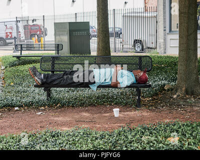 Homeless African-American or black man sleeping on a park bench in Montgomery Alabama, USA. - Stock Image
