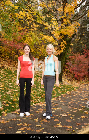 Portrait of two young women wearing fitness attire in autumn. - Stock Image