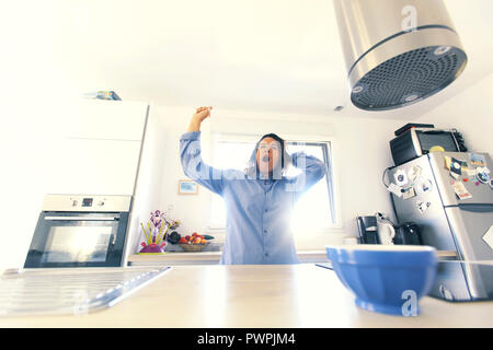Brunette woman in her kitchen in the morning. - Stock Image