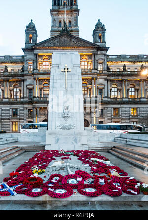 Many poppy wreaths laid in front of the Cenotaph in George Square in central Glasgow, with the City Chambers in the background. Scotland, UK - Stock Image