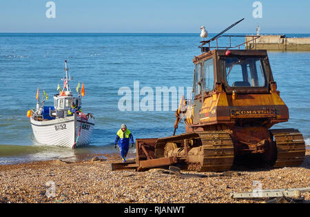 Hastings fishing boat about to be hauled ashore by a beach tractor. Hastings has the largest beach-launched fishing fleet in Europe - Stock Image