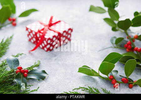 Christmas decorations, holly leaves with red berries. European Holly (Ilex aquifolium) leaves and fruit. - Stock Image