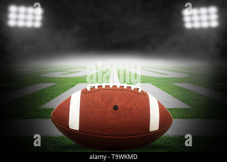 Close up of American football on stadium field with yard line markings and dramatic spotlight with rising fog background and copy space. - Stock Image