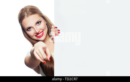 Cheerful woman with white empty paper board smiling and pointing isolated on white background - Stock Image