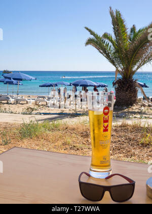 A perfect sunny day on the beach in Ayia Napa Cyprus, a cold KEO beer and views of the blue Mediterranean sea - Stock Image