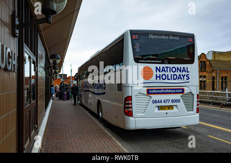 Middlesbrough Bus Station upper deck with passengers with luggage out side the Executive Lounge waiting to embark on a National Holidays coach - Stock Image