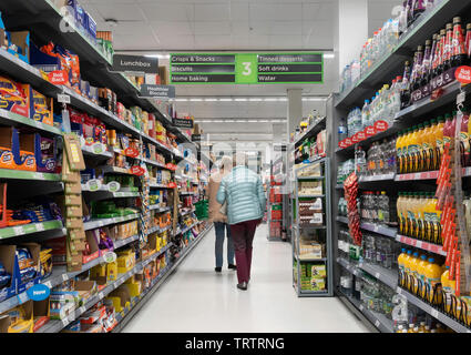 Two elderly women aisle displaying soft drinks, biscuits and crisps in Asda supermarket, UK - Stock Image