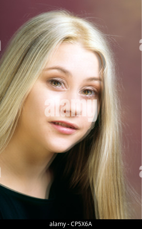 Double vision example picture of a pretty girl with long blond hair and green hazel eyes Head and shoulders Vertical - Stock Image