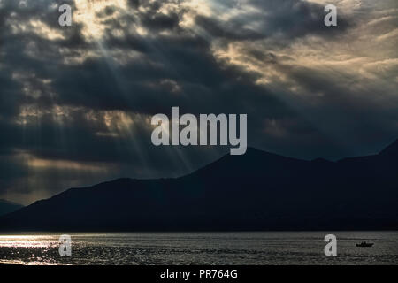 backlight panorama with sunbeams at sunset over the mountains and Maggiore Lake - Stock Image
