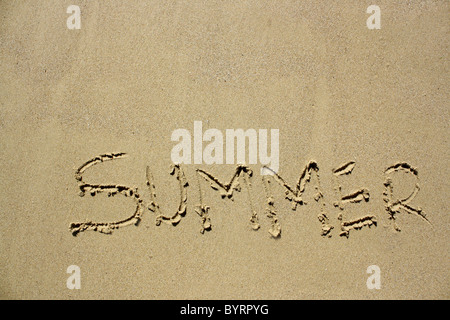 'Summer' written out in wet sand. Please see my collection for more similar photos. - Stock Image