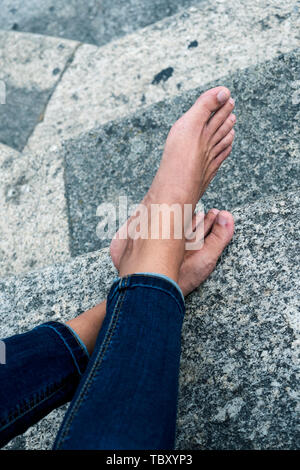 closeup of a young caucasian man, wearing denim trousers, resting barefoot sitting on a staircase on the street - Stock Image
