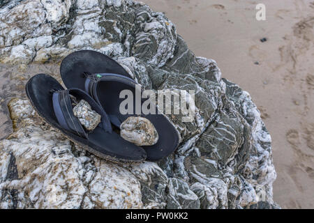 Beach sandals (weighted down with small stones as indicator the shoes are not 'Lost' or left by mistake). - Stock Image