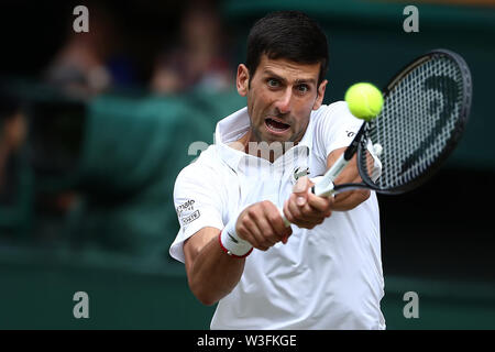 14th July 2019, The All England Lawn Tennis and Croquet Club, Wimbledon, England, Wimbledon Tennis Tournament, Day 13; Novak Djokovic (SER) with a backhand to Roger Federer (SUI) - Stock Image