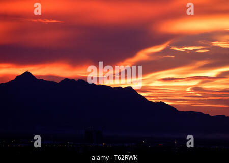 Burning red sky and clouds over Guning Serapi mountain at sunset in Kuching, Sarawak, Malaysia - Stock Image