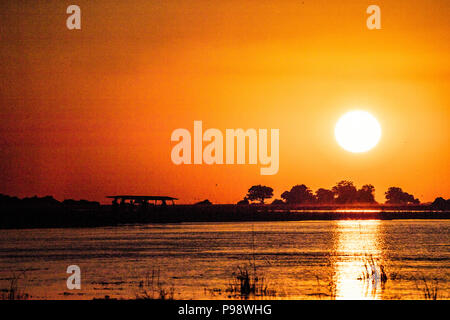Sunset over the Namibian bank of the Chobe River, as seen from Botswana - Stock Image