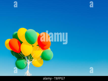 Colourful helium balloons against a blue sky background with copy space - Stock Image