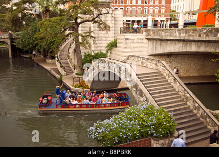 San Antonio River Walk texas tour boat passing under bridge one level below street traffic - Stock Image