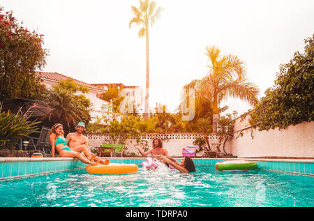 Group of happy friends relaxing in swimming pool - Young people having fun floating on air lilo during summer tropical vacation - Stock Image
