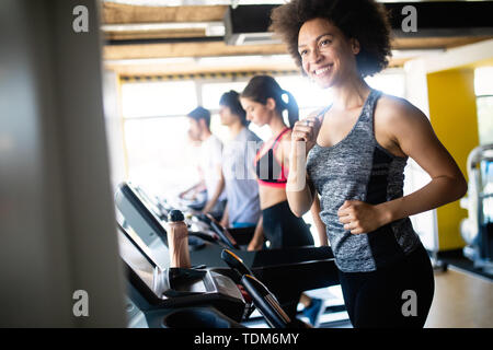 Young woman running on a treadmill in health club. - Stock Image