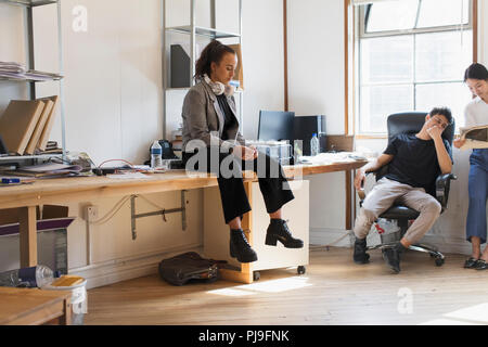 Creative businesswoman with headphones sitting on desk in office - Stock Image