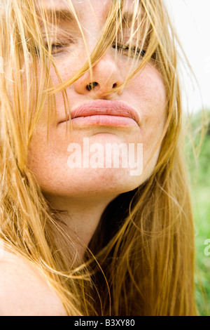 Close up portrait of attractive redheaded woman making a funny face - Stock Image