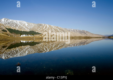 The Cluanie Inn and surrounding hills reflected in Loch Cluanie, Kintail - Stock Image