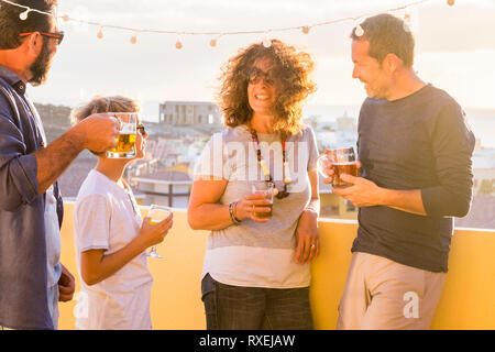 Group of friends enjoying outdoor with beer and drinks - mixed ages and generations caucasian people celebrating and staying together in friendship -  - Stock Image