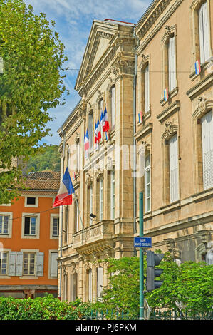 Tournon sur Rhone, Ardeche department, Rhone Alps, France and an ornate stone building with French tricoloure flags flying. - Stock Image