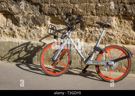a Mobike hire bike against a crumbling stone wall in Oxford - Stock Image