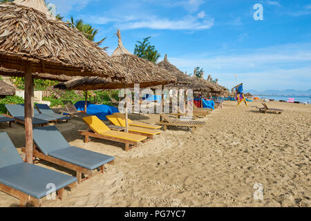 Deck chairs under straw umbrellas on the sand in An Bang beach, in Central Vietnam. The coastal town is situated near the UNESCO protected town of Hoi - Stock Image