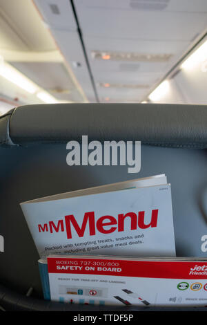 Back of the passenger seat on a  Boeing 737 showing magazine rack with flight menu and safety card - Stock Image