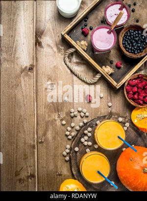 Fresh smoothies from berries and pumpkins. On a wooden background. - Stock Image