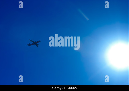 Airliner flying into the sun - Stock Image