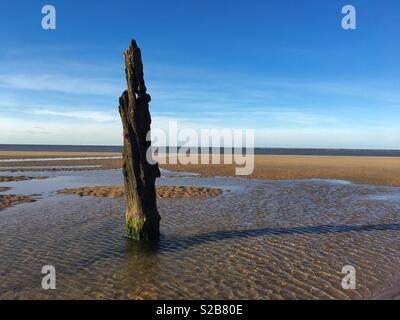 A single weathered post sticking out of Brancaster beach in Norfolk, England. - Stock Image