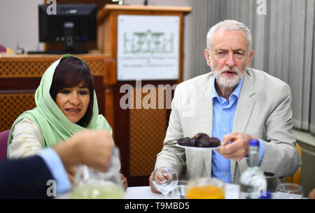 Labour leader Jeremy Corbyn with his wife Laura Alvarez break the fast during a visit to Regents Park Mosque in London. - Stock Image