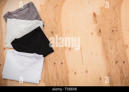Stack of arranged different coloured mens T-shirt on wooden background. Horizontal view. - Stock Image