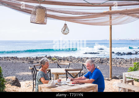 Successful retirement recreation, summer vacation concept. Retired mature couple enjoying a beautiful sunny day at the beach. Happy senior woman and m - Stock Image