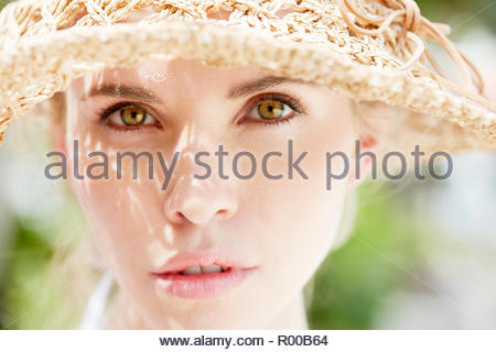 Portrait of young woman wearing straw hat - Stock Image