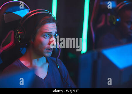 Shocked expressive young gamer with frowning forehead wearing headset with microphone keeping mouth open while looking at screen - Stock Image