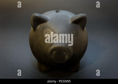 Front of the black piggy bank on the black background, the symbol of saving for a rainy day - Stock Image