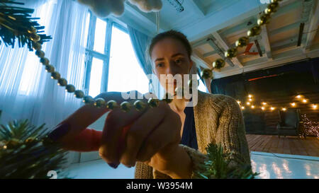 Woman decorating christmas tree with toys - Stock Image
