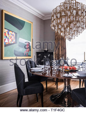Dining room with chandelier and modern painting - Stock Image