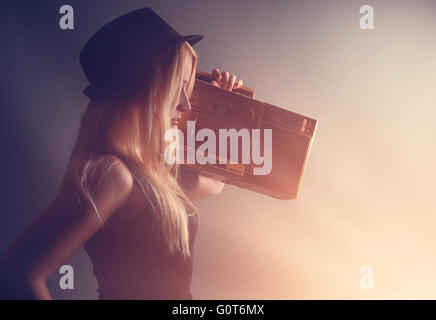 A blonde hipster girl is listening to a vintage gold boombox radio with a speaker for a music entertainment concept. - Stock Image