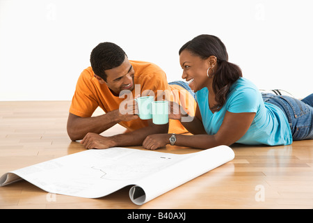 African American male and female couple with architectural blueprints toasting with their coffee cups - Stock Image
