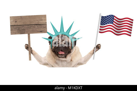 smiling pug puppy dog holding up American flag and blank wooden sign, wearing lady Liberty crown, isolated on white - Stock Image