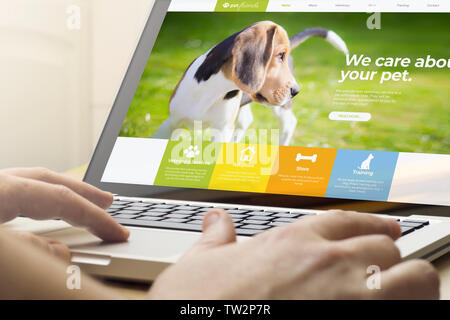 man using a laptop with pet website on the screen. Screen graphics are made up. - Stock Image